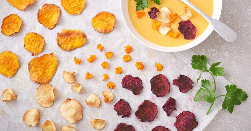Chips de verduras con chirivía, boniato, zanahoria y remolacha sobre papel de horno Albal®, con bol de crema de boniato.
