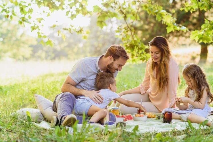 Familia feliz haciendo un picnic en el parque