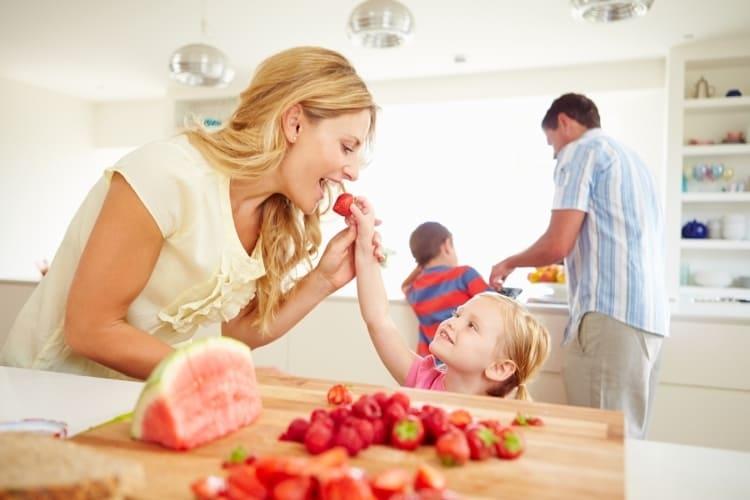 Familia feliz preparando el postre con fresas y sandía.