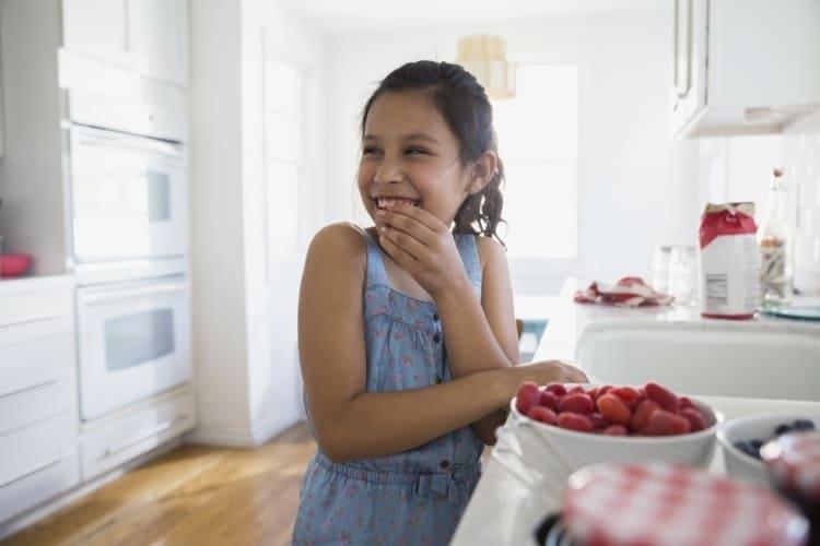 Niña sonriendo come frutos rojos en la cocina